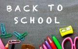 Back to school on chalkboard surrounded by school supplies
